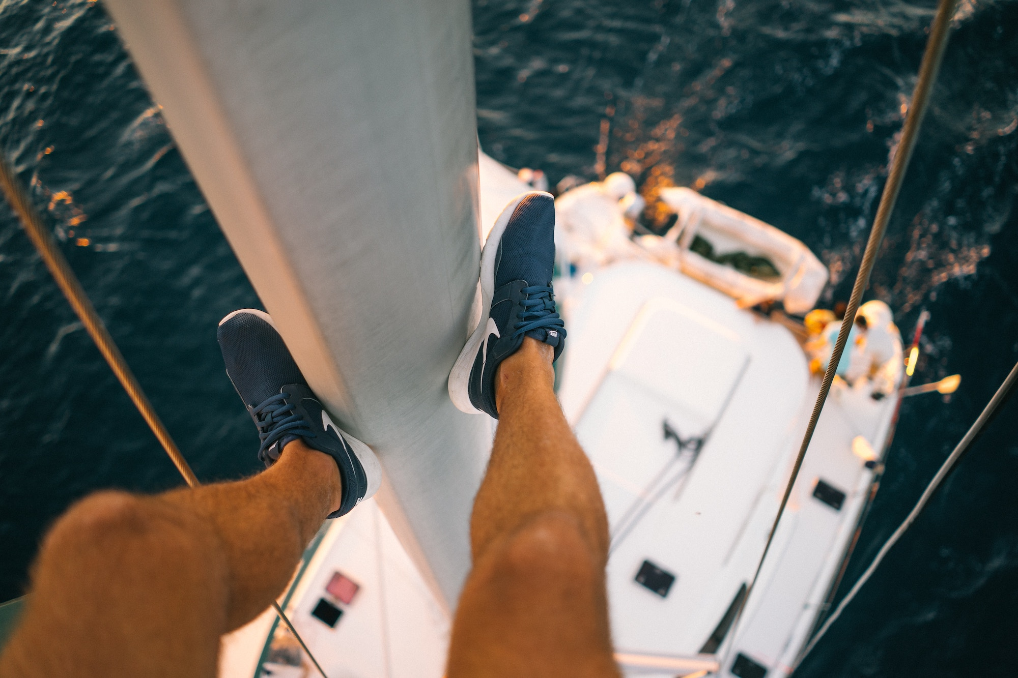Man looking down from the mast of a yacht